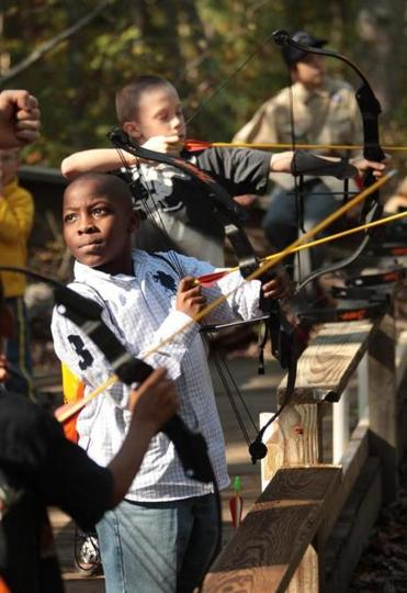 Trashaun Cairo, 8, takes archery lessons at the Boy Scout pumpkinfest in Milton.